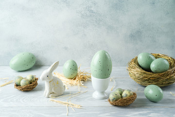 Easter holiday decorations with easter eggs, bunny and bird nest on wooden table