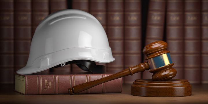 Labor law concept. Gavel  with concstruction hard hat and books.