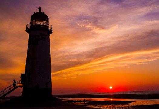 Coastal photograph of a lighthouse at sunset