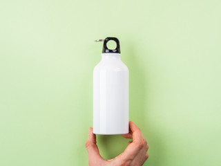 Zero waste concept - white metal reusable water bottle held by female hand. Flat lay on green...