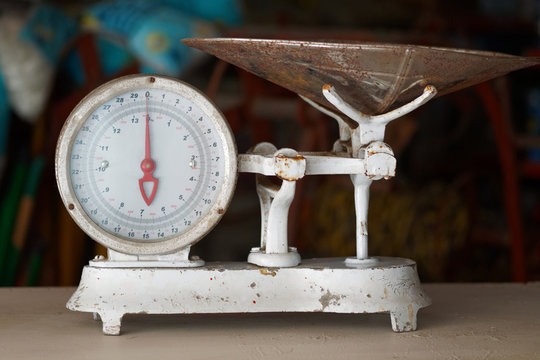 Old white vintage weight scale on table.
