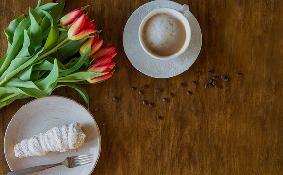 Top view of bouquet of red tulips, coffee and a cake on a wooden, rustic table, vintage look