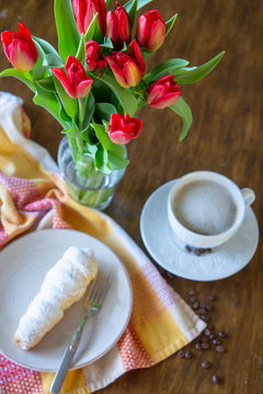 Bouquet of red tulips on a wooden coffee table with white coffee and a dessert plate, brunch theme