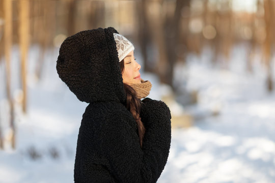 Winter happy woman relaxing breathing cold air outside young people lifestyle. Asian girl with closed eyes breathing wellness and health in forest wearing hooded jacket and hat.