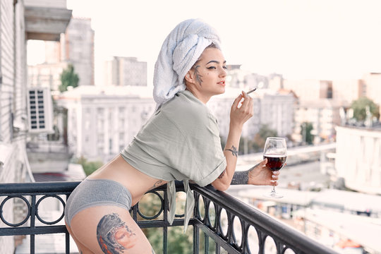 Home Leisure. Young woman in underwear and towel standing on balcony with glass of wine smoking cigarette looking aside smiling playful