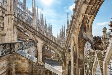 Fototapete - Milan Cathedral roof, Italy, Europe. Milan Cathedral or Duomo di Milano is top landmark of Milan city. Beautiful Gothic architecture of Milan against blue sky.
