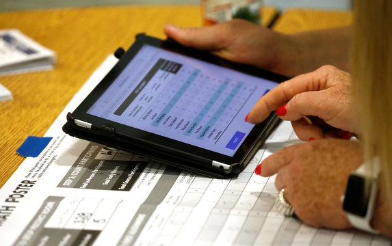 Nevada Caucus workers tally votes and report them to the Nevada Democratic Party through an Ipad in Henderson