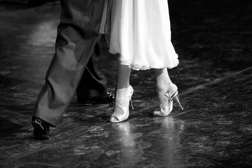 Graceful lines of legs of Argentina tango dancers in black and white