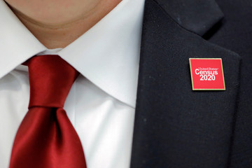 A United States Census 2020 pin is worn by Jeff T. Behler, Regional Director at the New York Regional Census Center, at an event where U.S. Rep. Alexandria Ocasio-Cortez (D-NY) spoke at a Census Town Hall at the Louis Armstrong Middle School