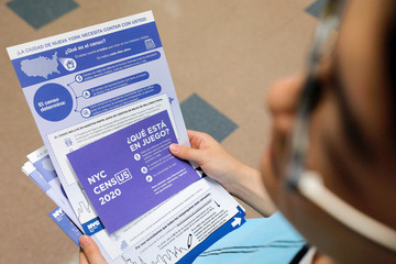 A person holds census information at an event where U.S. Rep. Alexandria Ocasio-Cortez (D-NY) spoke at a Census Town Hall at the Louis Armstrong Middle School in Queens, New York City