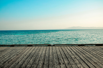 gray wooden deck of pier and blue summer sea with sky