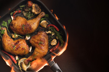 Wall Mural - Top view of grilled chicken thigh with various vegetables on pan on the flaming grill on black background..