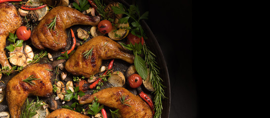 Wall Mural - Top view of grilled chicken thigh with various vegetables on pan on black background..