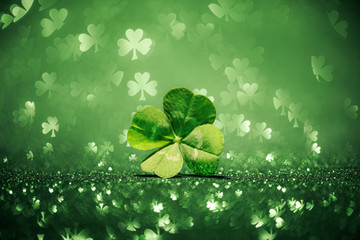 Lucky four leaf clover surrounded by sparkling shamrock shapes