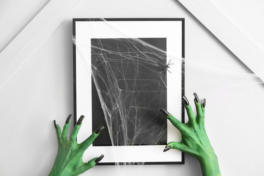 Hands of witch near photo frame indoors. Halloween celebration