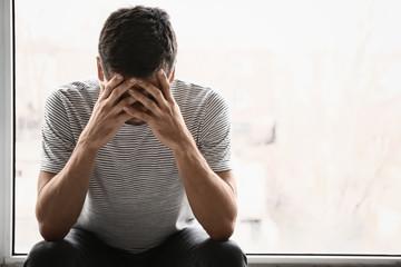 Depressed young man near window