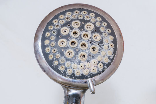 Close-up of limescale on shower head. Calcification of a shower head in bathroom.