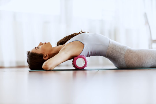 Close up of attractive slim young woman lying on the backs and stretching it with roller.