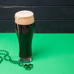 Obraz Glass of dark stout beer and traditional clover shaped decor on green table - fototapety do salonu