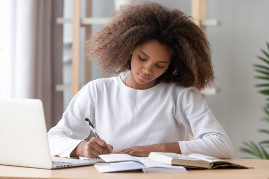 Focused african american school girl studying writing essay doing homework