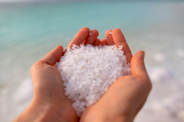 Close-up of the salt from the Death Sea in Jordan in woman<s hands . Papier Peint