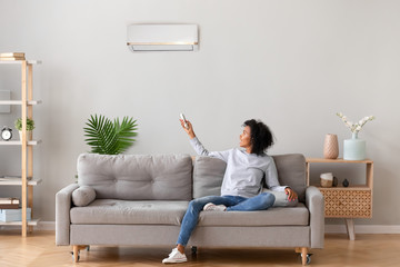 Happy african woman sitting on sofa switching on air conditioner Fotobehang