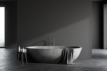 Stone bathtub in spacious grey bathroom