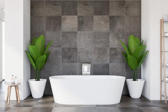 Bathtub and plants in tiled bathroom interior