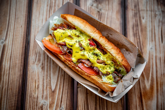 Philly cheese steak sandwich with meat, vegetables, cheese and sause in box on wooden table. street food