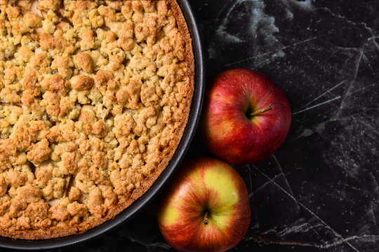 European apple pie with topping crumbles in springform pan on right side and blank copy space on black marbel background to left side