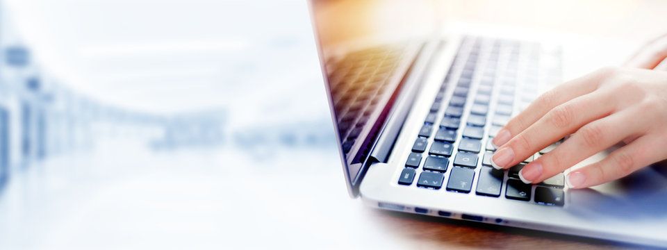 Business woman working on modern computer banner or panorama. Person buying online at internet. Laptop keyboard detail with hands copy space for text.