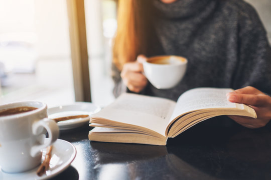 Closeup image of a woman reading a book while drinking coffee in cafe
