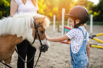 Cute little girl and her older sister enjoying with pony horse outdoors at ranch.. Wall mural