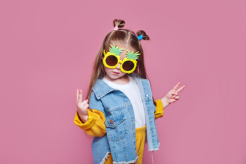 Summer fashion concept. cheerful little girl in big pineapple sunglasses on pink background Fotobehang