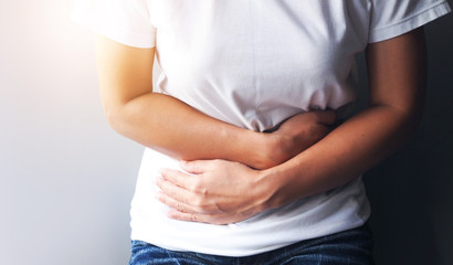 Asian women suffering with severe stomach pain, Stomach ache or menstrual pain.