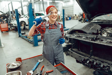 Cheerful young mechanic having fun at work
