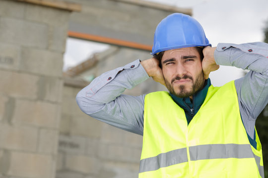 construction worker covering ears to ignore annoying loud noise