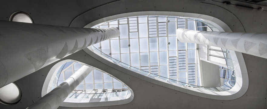 Super wide angle of a white atrium with skylight taken from below with columns that extend upwards