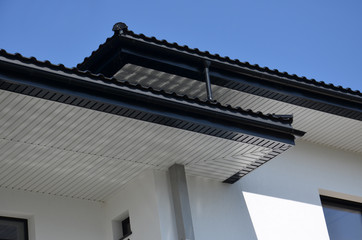 Roof overhang with rain gutter system against a blue sky. Black rain gutter system