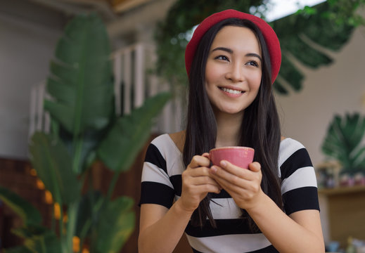 Young Asian woman drinking coffee in cafe. Portrait of positive hipster girl holding cup of tea. Korean model wearing stylish red beret posing for pictures and smiling. Coffee break concept