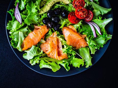 Salmon salad - smoked salmon and vegetables on black stone background