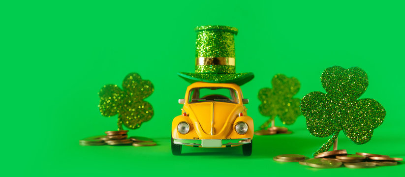 Minsk, Belarus - February 2020: holiday of St. Patricks Day A yellow toy car is carrying a hat and clover holiday symbol on a green background. Holiday Irish Patrick's Day postcard with retro car