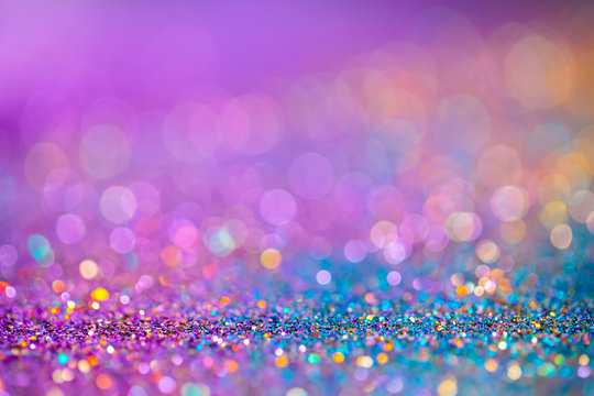Decoration twinkle glitters background, abstract blurred backdrop with circles,modern design overlay with sparkling glimmers. Blue, purple and golden backdrop glittering sparks with glow effect