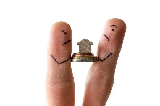 Zwei Fingermännchen streiten sich um Geld und Haus als Symbol für Scheidung