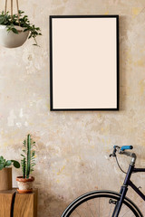 Modern composition of living room interior with black mock up poster frame, wooden cube, plant, cacti, hipster bike and personal accessories. Stylish home decor. Grunge wall. Wabi sabi. Template.