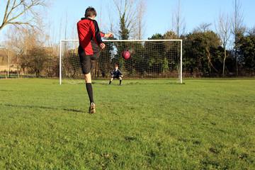 Teenage boy taken a football penalty kick.