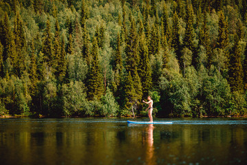 Man rowing oar on sup board blue lake water paddleboard background of forest
