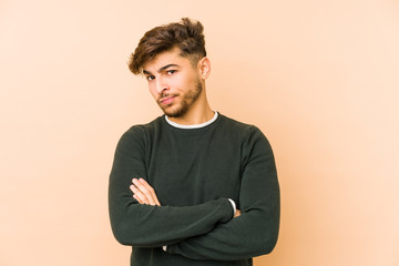 Young arabian man isolated on a beige background frowning face in displeasure, keeps arms folded. Wall mural