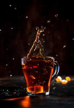 Splash in glass cup of black tea with natural steam on brown background