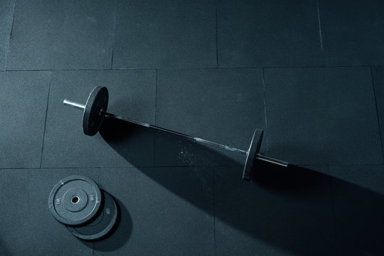 Fitness equipment for workout in Gym. Barbell with two weights plates on floor. Weight Olympic Bar Mockup Template Horizontal photo. Bright side light, sharp shadow. Top view